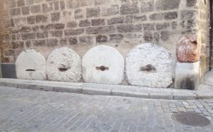 Seville mill stones protecting walls of buildings.