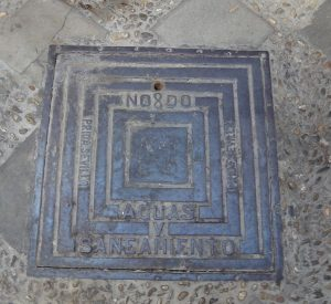 NO8DO. Allegiance to the King on a drain cover.